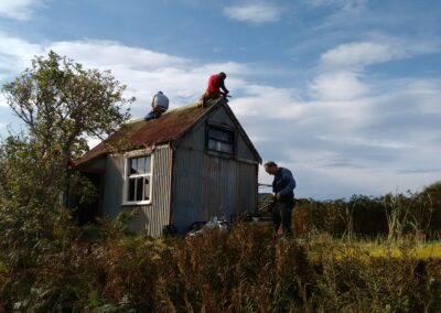 Volunteers remove old ridge flashing from museum roof Isle Martin