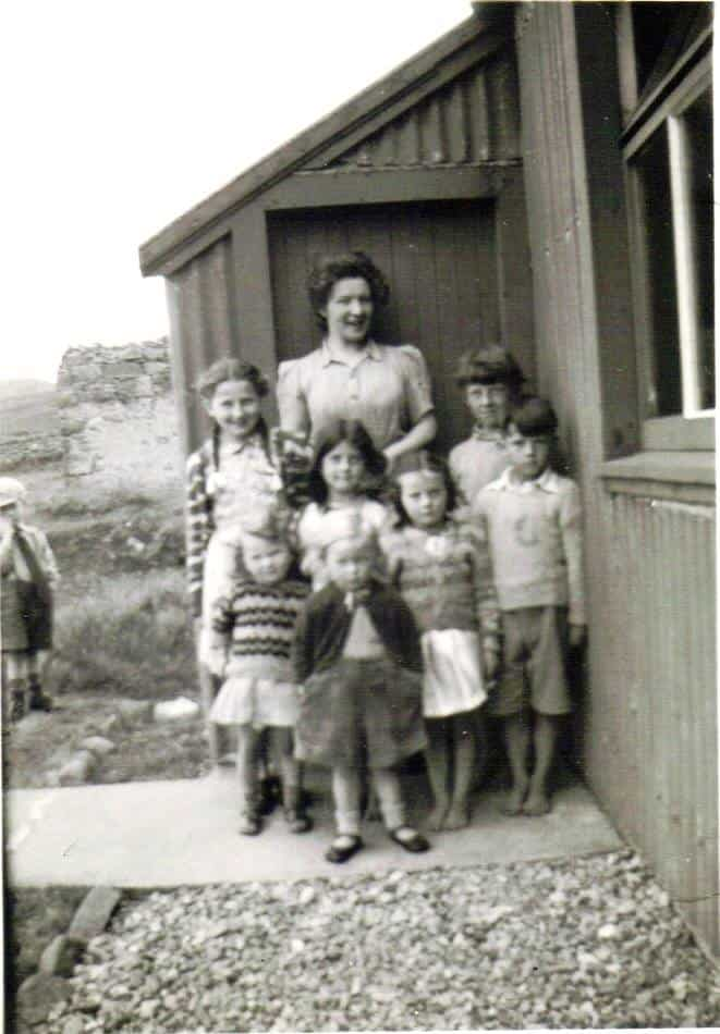 Children and teacher outside New School Isle Martin - old photo